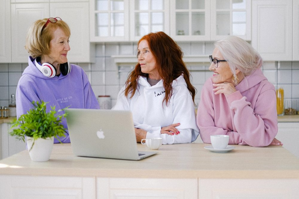 Group of older women conversing in kitchen at table.