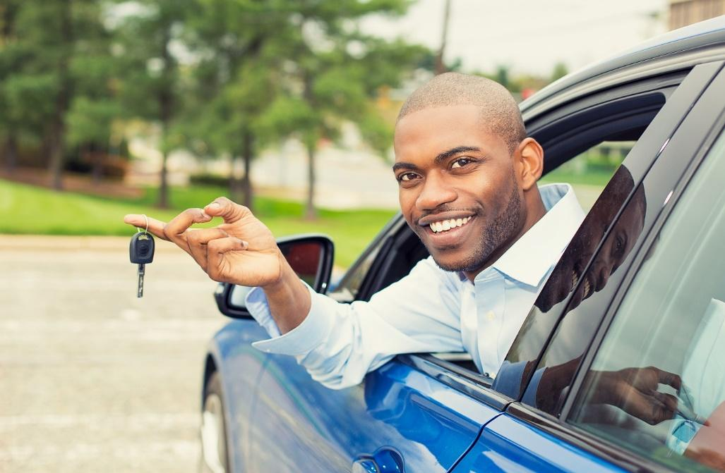 Man in the driver's seat of a new car showing his new car keys
